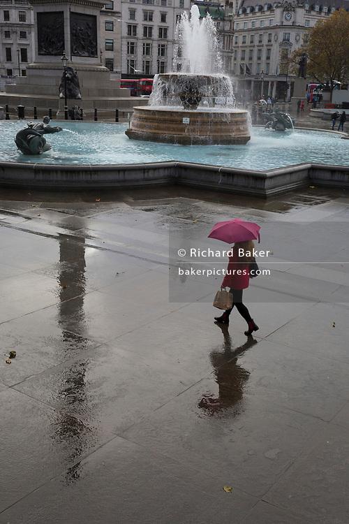 A lady walks through Trafalgar Square during a rain shower, on 12th November 2019, in London, England.