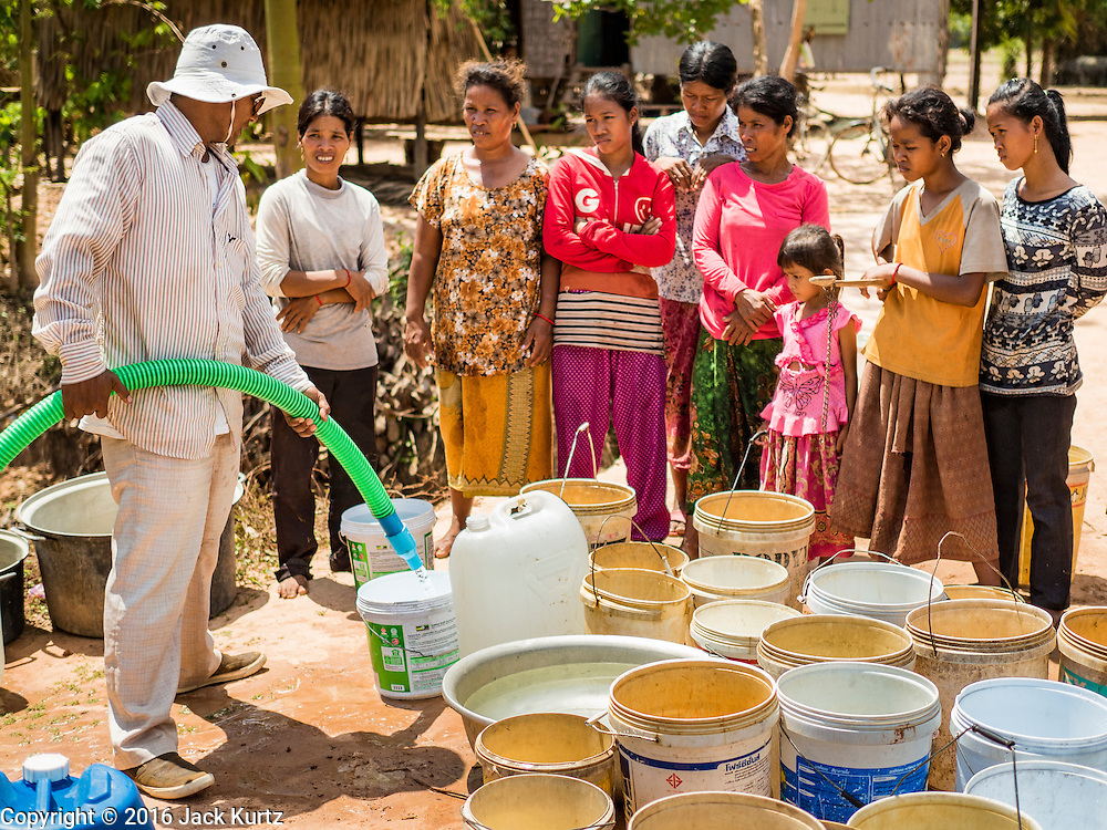 03 JUNE 2016 - SIEM REAP, CAMBODIA: Villagers wait as their water jugs are filled by a Water on Wheels volunteer (left) at a water distribution point in Sot Nikum, a village northeast of Siem Reap. Wells in the village have been dry for more than three months because of the drought that is gripping most of Southeast Asia. People in the community rely on water they have to buy from water sellers or water brought in by NGOs. They were waiting for water brought in by truck from Siem Reap by Water on Wheels, a NGO in Siem Reap. Cambodia is in the second year of  a record shattering drought, brought on by climate change and the El Niño weather pattern. There is no water to irrigate the farm fields and many of the wells in the area have run dry.     PHOTO BY JACK KURTZ