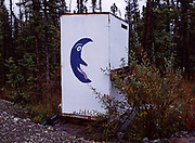 Outhouse with large painted crescent moon with face.  Note fine peppering of birdshot to the right of the moon -- Someone shot the shitter!  Glennallen, Alaska.