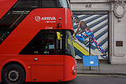 Red bus and stylish and athletic model on a billboard for clothing retailer H&M, in central London. We see a female adventurer wearing outdoor clothing, climbing up a diagonal slope on the billboard, the main colour being a yellow slant echoed by the lines painted on the ground, where London buses park before starting their routes. In 1947 Hennes women's clothing store opened in Västerås, Sweden. Today the H&M Group offers fashion for everyone under the brands of H&M, COS, Monki, Weekday, Cheap Monday and & Other Stories, as well as fashion for the home at H&M Home.