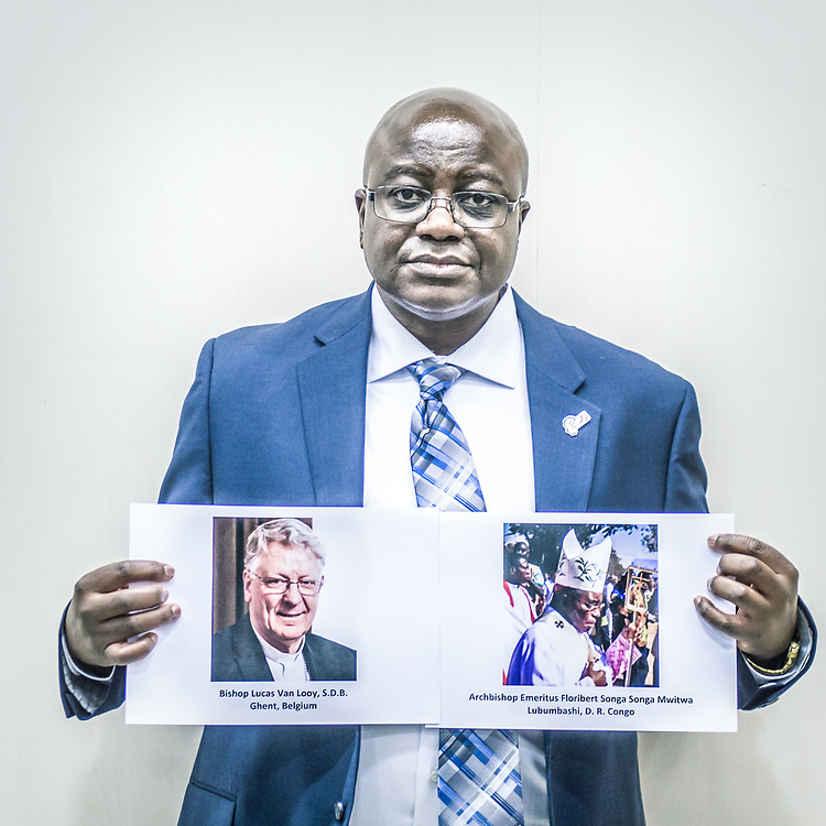 2018<br /> Benjamin Kitobo, a victim and activist from Congo, poses for a portrait showing pictures of two bishops, Lucas Van Looy and Floribert Songa Songa Mwitwa Lubumbashi from Congo that cover the abusers. © Simone PadovaniAwakening