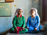 Portrait of two Cham women wearing traditional white headscarfs and Ao Dai, the national Vietnamese dress in Song Pha village, Lam Dong province, Central Vietnam