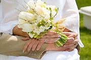 Marriage - bride and groom hold the bridal bouquet. Hands Only
