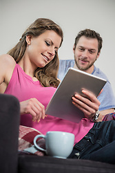 Couple using digital tablet in living room, Munich, Bavaria, Germany