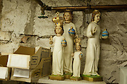 A group of small religious statues on a shelf, some of which wear crowns Martin has made.