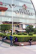A man photographs his female companion outside the Ambiance Mall, Saket, New Delhi, India