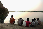 Six boys are sitting on the banks of the polluted Ganges River in Kanpur, Uttar Pradesh, near the tannery area of Jajmau. Sustaining life for thousands of years along the Indo-Gangetic plains, the river's ecosystem is in grave danger of being damaged beyond repair.