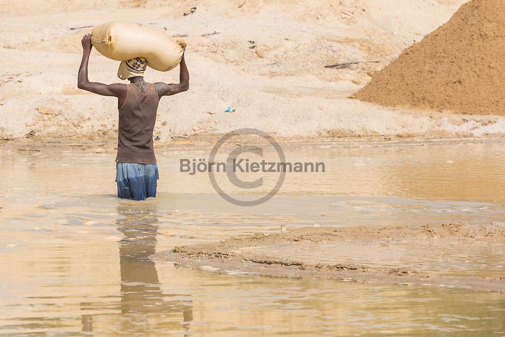 Tongo Field, Sierra Leone - 03.12.2015 <br /> <br /> The surrounding area of Tongo Field , also called Tongo , is one of the most involved in the diamond - mining region of Sierra Leone. Workers carry heavy sacks of sand, which other miners washed in riddle screens. The empty mine areas are then barren sandy deserts.<br /> <br /> Die Umgebung von Tongo Field, auch Tongo genannt, ist eine der am staerksten im Diamanten-Abbau involvierten Region von Sierra Leone. Arbeiter trage Sand in schweren Saecken ab, der von anderen Minenarbeitern in Sieben gewaschen wird. Zurück bleibt eine unfruchtbare Sandwüste.