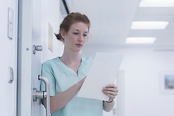 Young nurse reading medical charts while leaning  by door