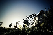 Low angle view of a young man jumping his bike off the roof of a building in Santa Barbara, California (digital composite). (releasecode: jk_mr1007) (Model Released)