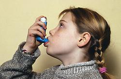 Young girl using an asthma inhaler,