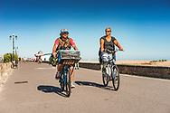 Young adult couple riding bikes along the promenade in Worthing with a small dog in a basket under blue sky on a summers days.