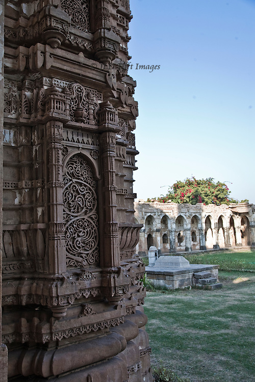 Friday mosque, Champaner-Pavagadh Archaeological Park.  Mughal ornament in a provincial style locally known as Indo-Saracenic.  Tomb in the center of the precinct, arcaded enclosure wall beyond.