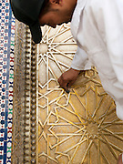 A man polishes the large, decorative door at the Royal Palace Dar el-Makhzen in Fes, Morocco