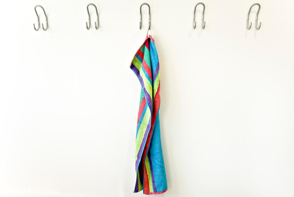 Ein Handtuch hängt an einem Haken eines Umkleideraumes      towel in cloak room   
