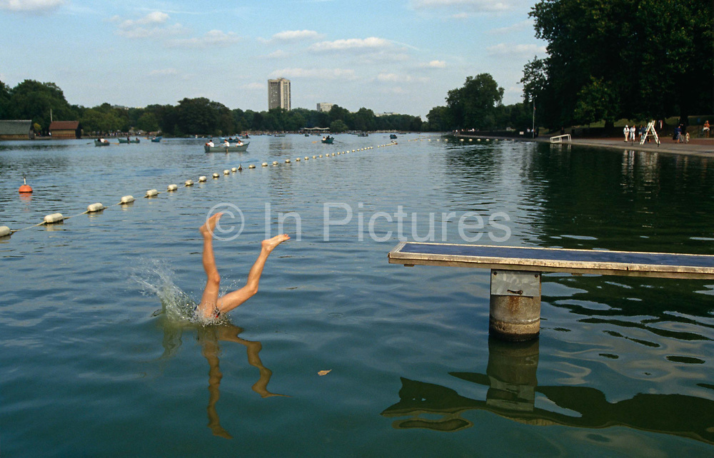 A pair of awkwardly splayed legs disappear into the cold, murky waters of the Serpentine Lake in London's Hyde Park. Having just dived head-first off a platform that juts out into the lake, the person is half in and half out and the splash is frozen in time. He or she is in incopetent diver with such ungainly plunge into the waters. It is otherwise a quiet moment. The water is largely undisturbed apart from the dive and buoy markers float to for a boundary line to keep rowing boats and bathers apart. This bathing area is where the normally busy Serpentine Swimming Club have the use of this Royal lake known as Lansbury's Lido. It is now normally open only in the summer, but one traditional event occurs each year on New Year's Day, when the ice is broken and brave bathers dive into the cold waters of the lake. The Serpentine will be used for the swimming leg of the triathlon at the London 2012 Olympics. The Serpentine gets its name from its supposedly snakelike, curving shape. It was formed in 1730 when Queen Caroline, wife of George II, ordered the damming of the River Westbourne and other natural ponds in Hyde Park.