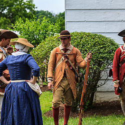Lancaster, PA, USA - June 9. 2012: Colonial woman talking to American soldiers at a British America reenactment camp.