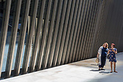 Beneath new architecture, two ladies walk along Bevis Marks in the City of London, the capitals financial district, on 17th June 2019, in London, England.