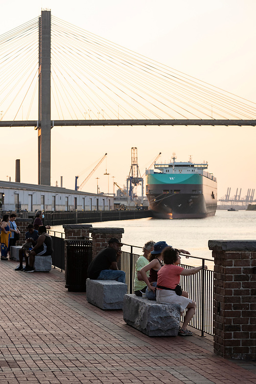 Savannah, Georgia, USA - July 29, 2021: Visitors to Savannah's waterfront sit on stone benches at sunset. A vehicle carrier ship named Tamesis is docked in the background.