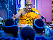 "24 JUNE 2017 - BANG KRUAI, NONTHABURI: A Buddhist monk preaches during a ""resurrection"" or rebirthing ceremony at Wat Ta Kien (also spelled Wat Tahkian), a Buddhist temple in the suburbs of Bangkok. People go to the temple to participate in a ""Resurrection Ceremony."" Thai Buddhists believe that connecting people by strings around their heads, which are connected to a web of strings suspended from the ceiling, amplifies the power of the prayer. Groups of people meet and pray with the temple's Buddhist monks. Then they lie in coffins, the monks pull a pink sheet over them, symbolizing their ritualistic death. The sheet is then pulled back, and people sit up in the coffin, symbolizing their ritualist rebirth. The ceremony is supposed to expunge bad karma and bad luck from a person's life and also get people used to the idea of the inevitability of death. Most times, one person lays in one coffin, but there is family sized coffin that can accommodate up to six people. The temple has been doing the resurrection ceremonies for about nine years.     PHOTO BY JACK KURTZ"