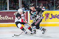 KELOWNA, CANADA - OCTOBER 23: Jared Bethune #21 of Prince George Cougars stick checks Tyson Baillie #24 of Kelowna Rockets as he skates with the puck up the ice during first period on October 23, 2015 at Prospera Place in Kelowna, British Columbia, Canada.  (Photo by Marissa Baecker/Shoot the Breeze)  *** Local Caption *** Jared Bethune; Tyson Baillie;