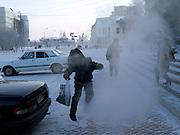 Junge springt ueber die Abgase eines geparketen Autos mit laufendem Motor in Jakutsk. Jakutsk wurde 1632 gegruendet und feierte 2007 sein 375 jaehriges Bestehen. Jakutsk ist im Winter eine der kaeltesten Grossstaedte weltweit mit durchschnittlichen Winter Temperaturen von -40.9 Grad Celsius. Die Stadt ist nicht weit entfernt von Oimjakon, dem Kaeltepol der bewohnten Gebiete der Erde.<br /> <br /> Boy jumping over the fumes of a parked running car in the city center of Yakutsk. Yakutsk was founded in 1632 and celebrated 2007 the 375th anniversary - billboard announcing the celebration. Yakutsk is a city in the Russian Far East, located about 4 degrees (450 km) below the Arctic Circle. It is the capital of the Sakha (Yakutia) Republic (formerly the Yakut Autonomous Soviet Socialist Republic), Russia and a major port on the Lena River. Yakutsk is one of the coldest cities on earth, with winter temperatures averaging -40.9 degrees Celsius.
