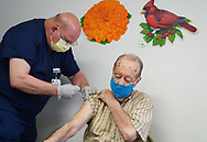 Critical care registered nurse Timothy Brewer, left, injects Daniel Rudy, right, with his second dose of the Moderna vaccine as Lehigh Valley Health Network brought their mobile vaccination clinic to Majestic House on May 6, 2021, which offers low income housing to Seniors 55 years and over, in Tamaqua, Pennsylvania.