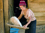 A Laoseng minority woman winnows rice outside her home in the remote and roadless village of Ban Phouxoum, Phongsaly province, Lao PDR. Ban Phouxoum is situated along the Nam Ou river (a tributary of the Mekong) and has been temporarily relocated due to the construction of the Nam Ou Cascade Hydropower Project Dam 6. The Nam Ou river connects small riverside villages and provides the rural population with food for fishing. But this river and others like it, that are the lifeline of rural communities and local economies are being blocked, diverted and decimated by dams. The Lao government hopes to transform the country into 'the battery of Southeast Asia' by exporting the power to Thailand and Vietnam.