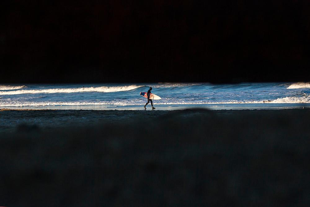 Feb 27, 2013; Virginia Beach; VA; A surfer walks into the water near 25th Street. Mandatory Credit: Peter J. Casey