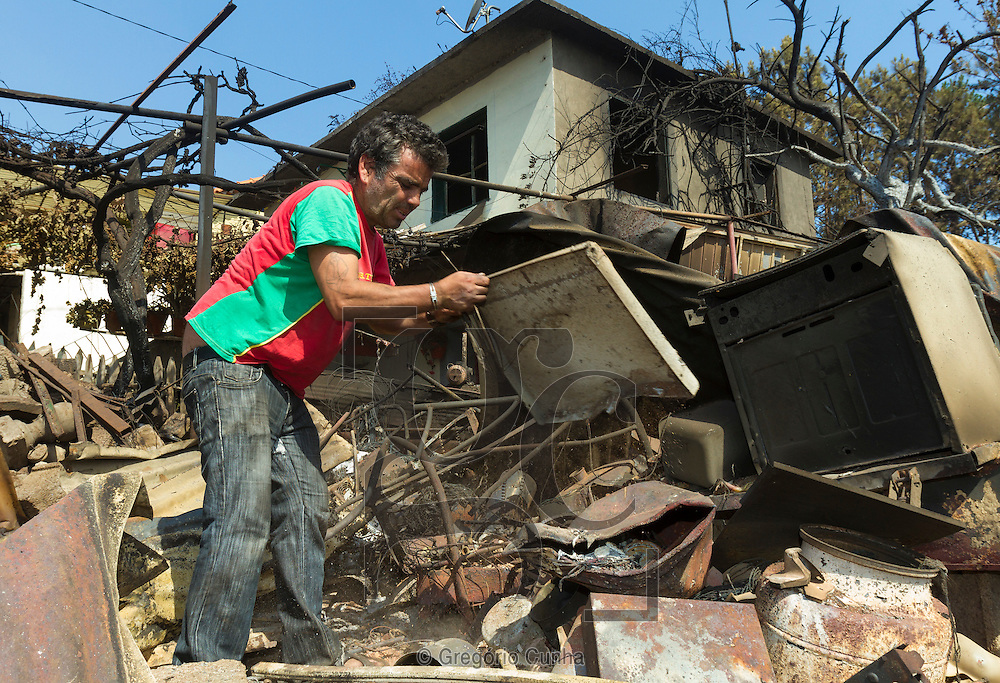 PORTUGAL, Gaula : Jose Nobre looks through the rubble of his burned house after a fire broke out in Gaula, some 20 km from Funchal, on Madeira Island, on July 20, 2012. Fires raged around the towns of Calheta, Ribeira Brava as well as in Santa Cruz, where one house was destroyed and a health centre, school and youth centre were evacuated as a precautionary measure. The problems started on July 18 evening when high temperatures and strong winds fanned a fire that broke out on the edge of the capital Funchal, gutting two houses and partially burning a third. PHOTO / GREGORIO CUNHA