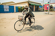 30 JANUARY 2013 - PHNOM PENH, CAMBODIA:  A man rides his bike on a main road near Phnom Penh, Cambodia.   PHOTO BY JACK KURTZ