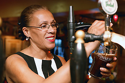 Woman working behind a bar in a pub,