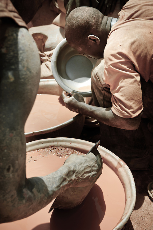 Stock photograph of African gold miners in Burkina Faso conducting grade control by panning ore to find gold nuggets.