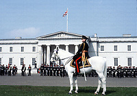 A commanding officer on the infamous white horse during the Sovereign's parade ceremony at Sandhurst. This parade marks the start of a career as an officer for the cadets pictured in the background. Photograph by Terry Fincher