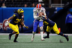 Florida Gators quarterback Feleipe Franks #13 is tackled by Michigan Wolverines defensive back Tyree Kinnel #23 during the Chick-fil-A Peach Bowl, Saturday, December 29, 2018, in Atlanta. ( Paul Abell via Abell Images for Chick-fil-A Peach Bowl)