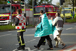 © Licensed to London News Pictures. Manchester, UK 16/05/2012: Two people wrapped in insulation sheets are given hot drinks and lead across the road at the scene of a fire in Greater Manchester. Twenty five firefighters tackle a blaze at a flat above H&A Tailors on the A34 Kingsway in Levenshulme. Two people were evacuated from the flat and taken to hospital. The main city-centre route was closed in both directions. Photo credit : Joel Goodman/LNP