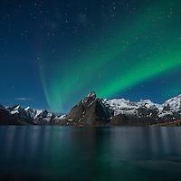 Northern Lights - Aurora Borealis shine in sky over Olstind mountain peak, Hamnøy, near Reine, Moskenesøy, Lofoten Islands, Norway