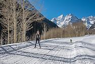 Skiing down Maroon Creek Road in winter in Aspen, Colorado.