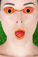 Closeup portrait of a woman wearing tanning bed glasses with strawberry in mouth against green