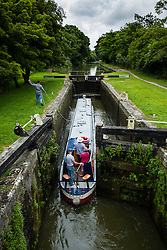 Narrow boat entering lock on Kennet and Avon Canal in Wiltshire England, United Kingdom