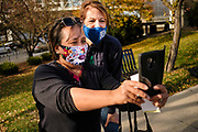 "31 OCTOBER 2020 - DES MOINES, IOWA: US Representative CINDY AXNE (D-IA) poses for a ""selfie"" with a voter wearing a Day of the Dead face mask at a ""Unity at the Polls"" rally across the street from the Polk County Auditor's Office in Des Moines. Axne is running for reelection. Her district, the most diverse in Iowa, runs from the southwest corner of Iowa through Des Moines. The rally was to support the right to vote for people of color and people from at risk communities. This is the last weekend of early voting before the 2020 US presidential election. An elections official said that by November 3, which is Election Day, about 45 percent of the registered voters in Polk County will have already voted.     PHOTO BY JACK KURTZ"