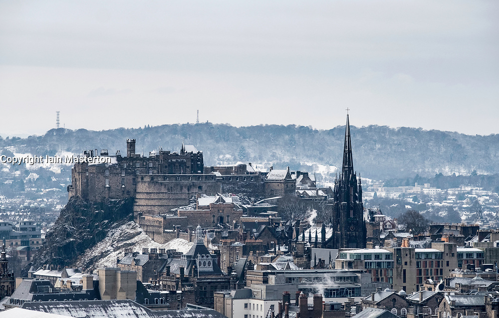 Snow falls on city of Edinburgh in December. Skyline view of city towards the Edinburgh castle from Salisbury Crags ,Scotland, UK.