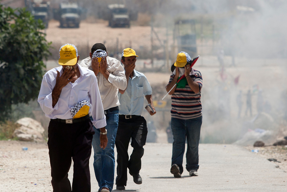 Palestinian protesters are trying to avoid tear gas, thrown by Israeli soldiers, during a protest against Israel's separation barrier in the West Bank village of Beit Nuba on June 04, 2010.