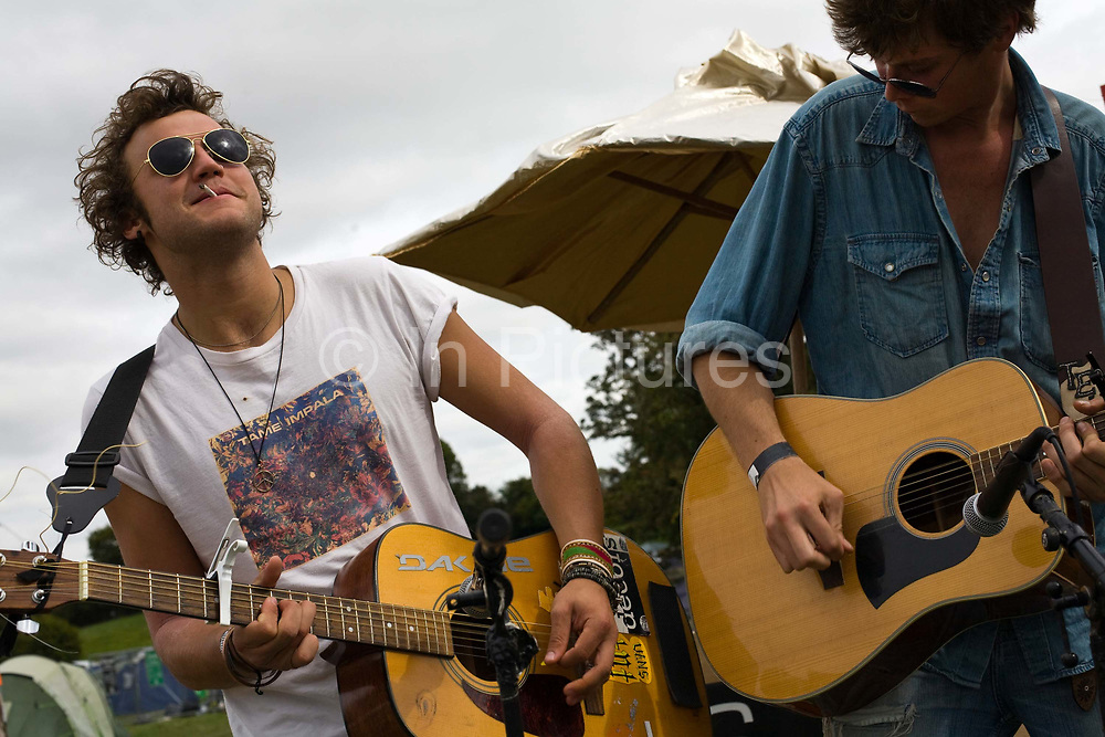Two musicians play guitar on a moveable stage at the Standon Calling Festival in Hertfordshire, UK<br /> Standon Calling is a small independent festival set among the hills in Herfordshire that showcases World Music, Indie Music and dance Music. It is one of the new, small and quirky boutique festivals which have become popular in the UK.