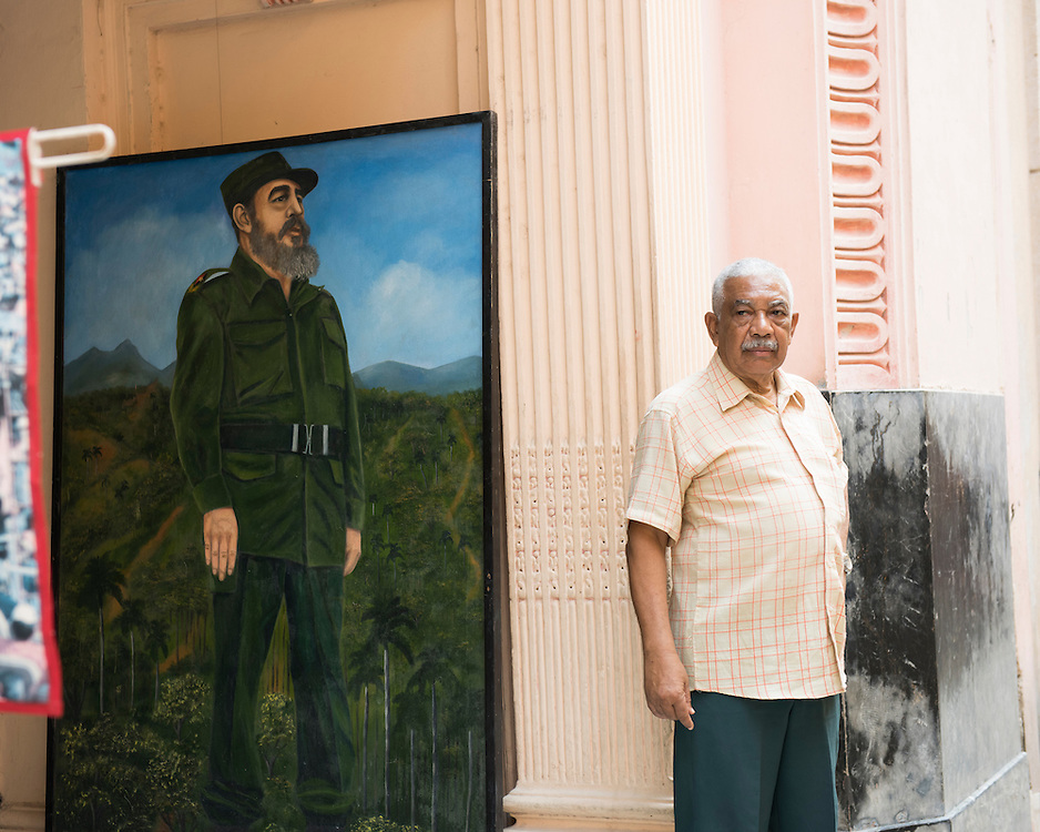 Havana, Cuba - October 2015:  A man stands in the street of Old Havana.  A realistic life-size painting representing Fidel Castro lies behind his back.