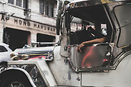 Manila, Philippines - July 27, 2019: The arm of a jeepney driver rests in a window while stopped at an intersection in the Chinatown area of Manila, Philippines.