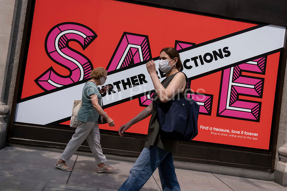 Shoppers wearing face masks walk past Selfridges whose Summer Sale is advertised in their window banners on Oxford Street in the West End on Covid Freedom Day. This date is what Prime Minister Boris Johnsons UK government has set as the end of strict Covid pandemic social distancing conditions with the end of mandatory face coverings in shops and public transport, on 19th July 2021, in London, England.