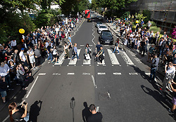 © Licensed to London News Pictures. 08/08/2019. London, UK. Beatles fans recreate the famous album cover photograph at the zebra crossing outside the Abbey Road studios in north London. The Beatles were photographed for the Abbey Road album cover 50 years ago today. Photo credit: Peter Macdiarmid/LNP