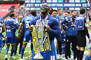 Adebayo Akinfenwa of AFC Wimbledon celebrates with the Sky Bet League 2 Play-off Trophy. Skybet football league two play off final match, AFC Wimbledon v Plymouth Argyle at Wembley Stadium in London on Monday 30th May 2016.<br /> pic by John Patrick Fletcher, Andrew Orchard sports photography.