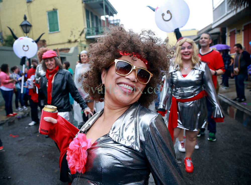 """23 Feb 2014. New Orleans, Louisiana.<br /> Sharon Berry walks the wet and soggy streets of the French Quarter with her disco divas at the 22nd Mystic Krewe of Barkus parade, the only officially licensed Mardi Gras krewe by and for canines. This year's parade is themed  """"Dogzilla: Barkus Licks the Crescent City."""" <br /> Photo; Charlie Varley/varleypix.com"""